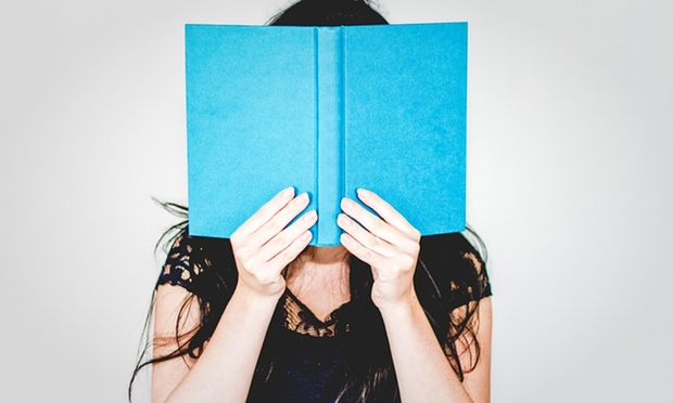 Female covering her face with a book